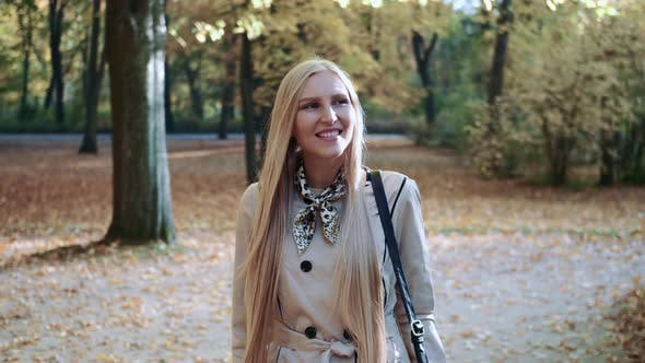 Thumbnail for Beautiful Young Blonde Girl Walking in the Park in Autumn and Smiling