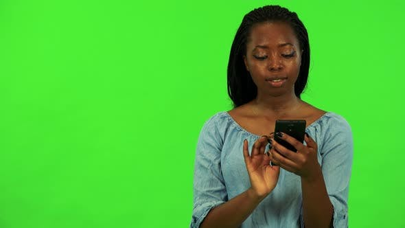 Thumbnail for A Young Black Woman Works on a Smartphone with a Smile - Green Screen Studio
