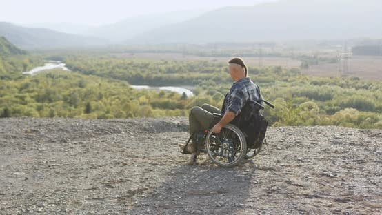 Thumbnail for Handicapped Man in Wheelchair Which Looking Around on the Top of Hill