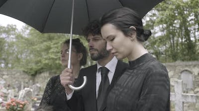 Family Mourning on graveyard at funeral