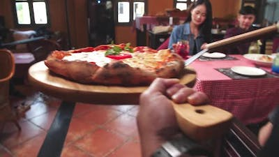 The Waiter Puts Pizza On The Table In The Restaurant