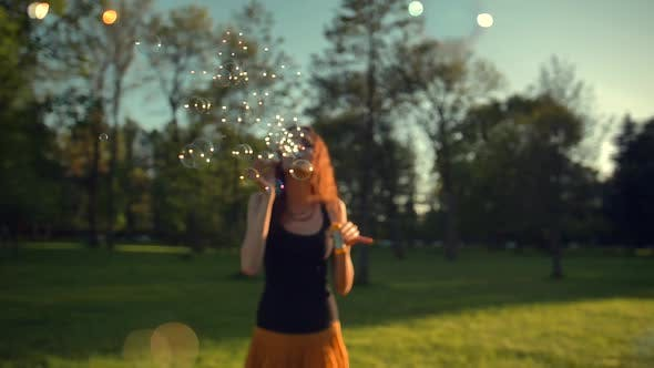 Thumbnail for Beautiful Young Redhair Woman Blowing Soap Bubbles Outdoors.