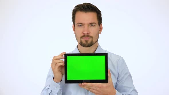 Thumbnail for A Young Man Shows a Tablet with Green Screen To the Camera and Slowly Smiles - White Screen Studio