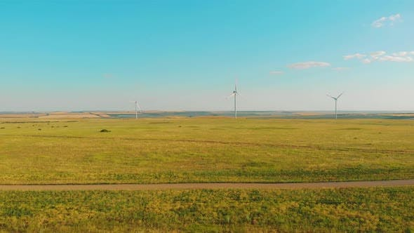 Windmills for Electric Power Production in the Meadow. Group of Windmills for Renewable Electric