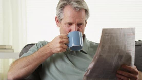 Thumbnail for Senior smiling reading newspaper