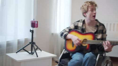 A Disabled Man is Playing the Guitar and Singing Songs Professionally