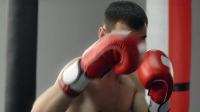 Boxer Man in Red Boxing Gloves Does Shadow Boxing and Trains at Boxing Club Fighter Man is Fighting