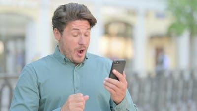 Outdoor Man Celebrating on Smartphone