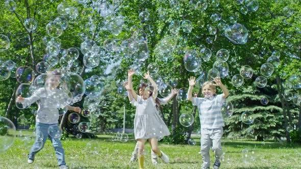 Cover Image for Adorable Kids Bursting Huge Bubbles in Park