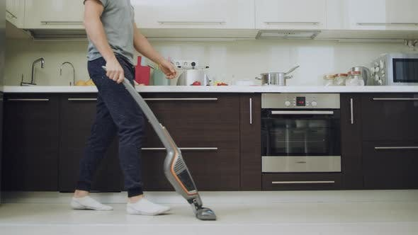Thumbnail for Caring Man Cleaning Floor with Vacuum Machine at Modern Kitchen.