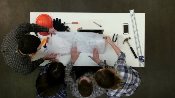 Thumbnail for Group of Architects Discussing Technical Drawings
