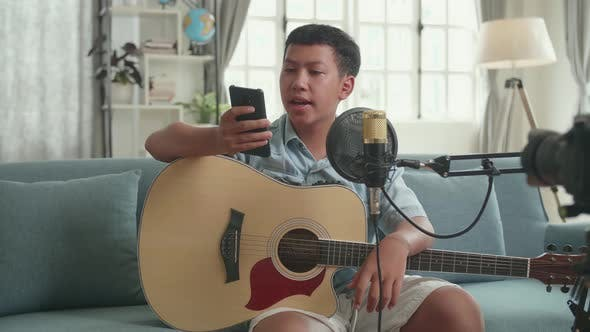 Asian Boy Is A Vlogger With Guitar Read Comment On Mobile Phone. The Boy Is Streaming