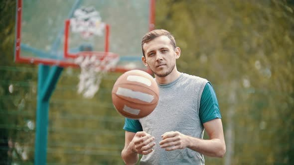 Thumbnail for A Man Standing on a Sports Ground and Throws Up the Basketball Ball
