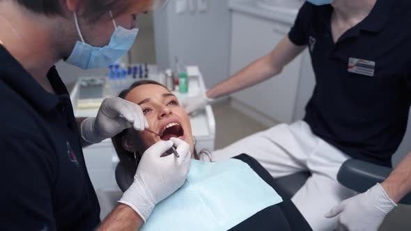 Dentist examines woman's teeth. Female's face with opened mouth in the dental chair.