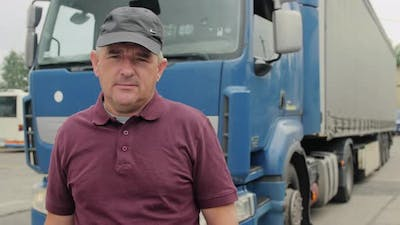 Professional Truck Driver Stands In Front Of Semi Truck