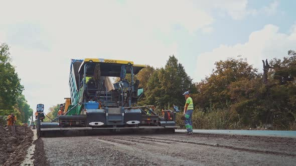 Workers with shovels laying new asphalt. Asphalt road construction.
