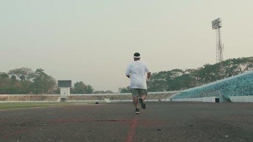 Overweight Man Running At Stadium
