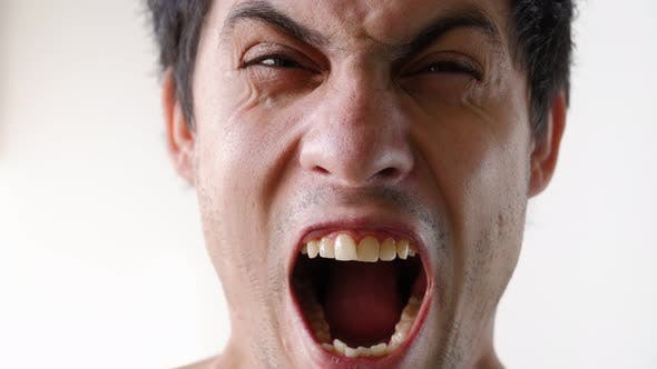Portrait Angry Guy Yells Directly Into Camera. Male Emotions Close-up