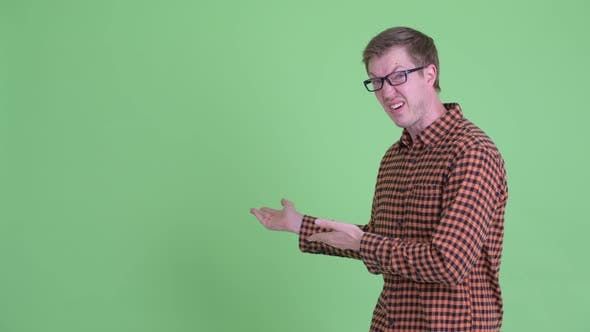 Thumbnail for Disgusted Young Hipster Man Showing Something To the Back