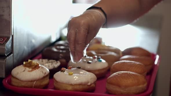 Thumbnail for Die gebackenen Donuts werden von Süßigkeiten dekoriert