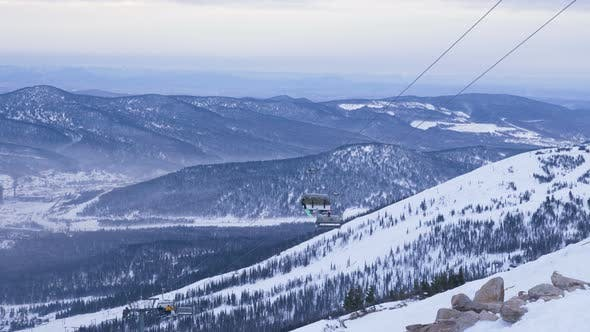 Thumbnail for Cabins of Ski Lift with Tourists Move Above Mountain Slope