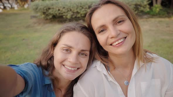 Thumbnail for Two Women Laying on the Grass and Take a Selfie Photo Together