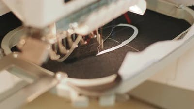 The automatic embroidery machine is working at high speed. Close-up