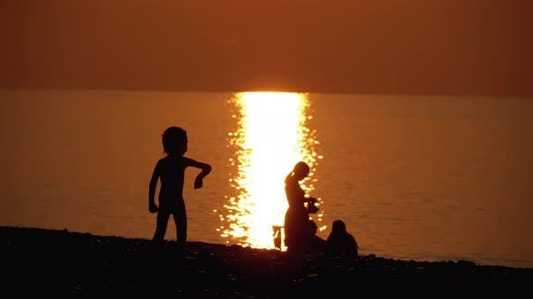 Thumbnail for Silhouette of a Happy Child at Sunset By the Sea Playing with a Toy Airplane, Happy Family