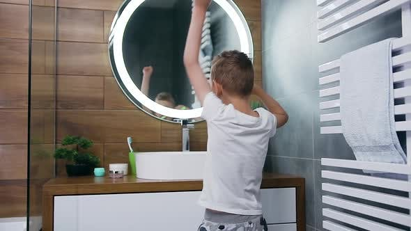 Funny Lucky 10-Aged Blond Boy which Dancing During Cleaning His Teeth in Front of Bathroom Mirror