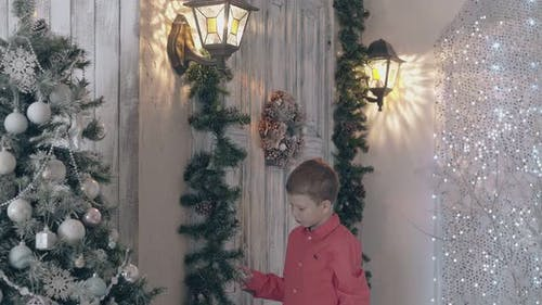 Schoolboy in Red Shirt Touches Pine Garland Decor in Room
