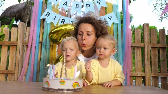 Single Mom Helps Her Twin Toddlers to Blow Candles Out at Second Birthday Party in the Garden