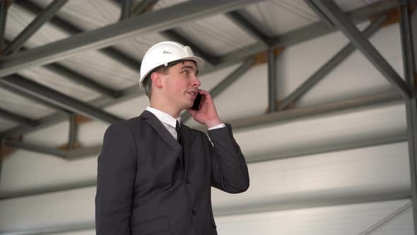 Thumbnail for A Young Man in a Helmet Speaks on the Phone at a Construction Site. The Boss in a Suit Is Talking on