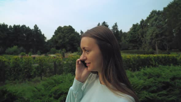 Thumbnail for Young Brunette Girl Slowly Passes Through the Park and Talking on the Phone
