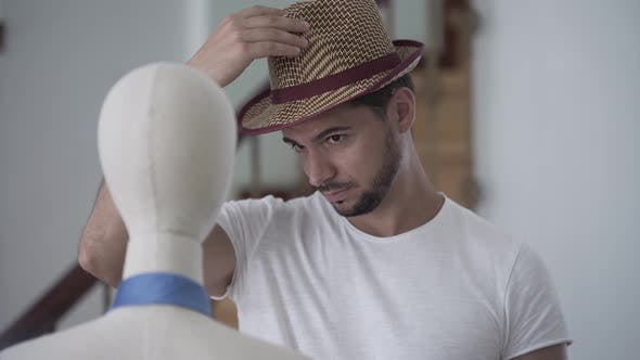 Cover Image for Portrait of a Bearded Man Putting His Hat on the Head of the Mannequin