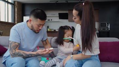 Joyful Asian Parents and Daughter Playing Doctor Game