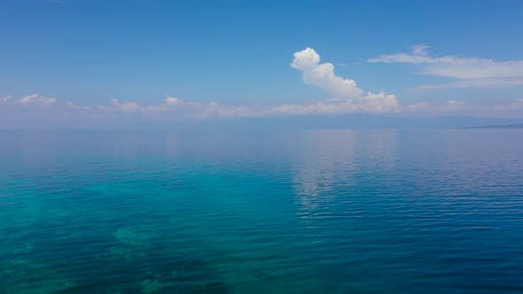 Thumbnail for Tropical Blue Sea and Blue Sky with Clouds. Mountains on the Horizon.