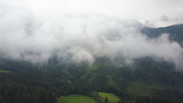 Thumbnail for Aerial Shot in Clouds, Camera Is Over Green Mountains and Fields