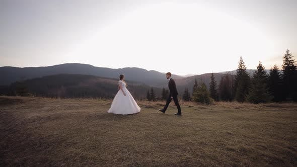 Newlyweds. Caucasian Groom with Bride on Mountain Slope. Groom Proposes