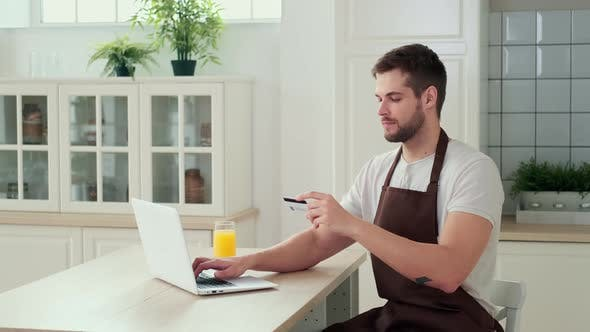 A Man Pays for Online Delivery of Food to His Home Using a Credit Card While Sitting in the Kitchen