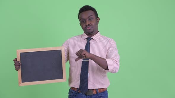 Thumbnail for Stressed Young African Businessman Holding Blackboard and Giving Thumbs Down