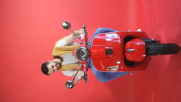 Portrait of a Serious Man Sitting on a Scooter in Isolation on a Red Studio Background, a Young Man