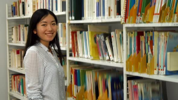 Thumbnail for Girl Puts Academic Journals on the Rack at the Library