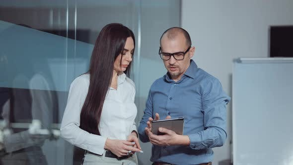 Businessman with tablet showing analytics to colleague