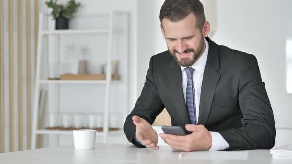 Thumbnail for Man Celebrating Success While Using Smartphone