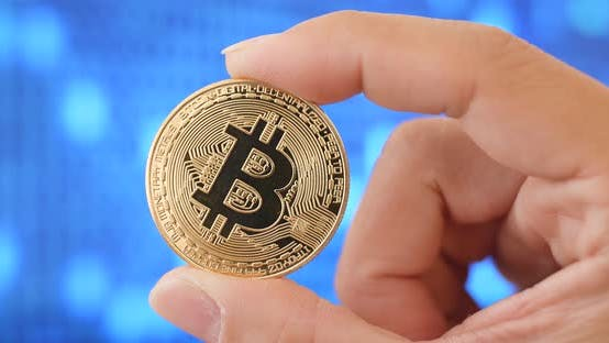 Thumbnail for Hand holding bitcoin over digital abstract background