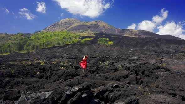 Thumbnail for Young Woman in Red Dress on Frozen Black Lava and Green Trees on the Slope of Volcano Batur on Bali
