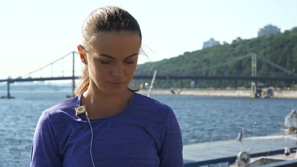Thumbnail for Woman Attaches Mp3 Player on Clothes and Wears Headphones, Looking Around