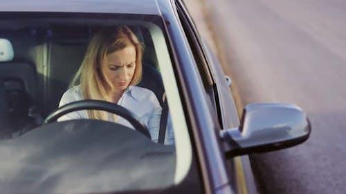 Woman Fastening Belt in Car