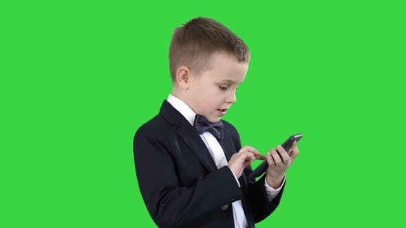 Young Boy in Elegance Suit Playing with Mobile Phone on a Green Screen, Chroma Key