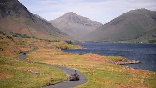 People driving on a road by the lake towards the mountains of the England Lake District - wide shot